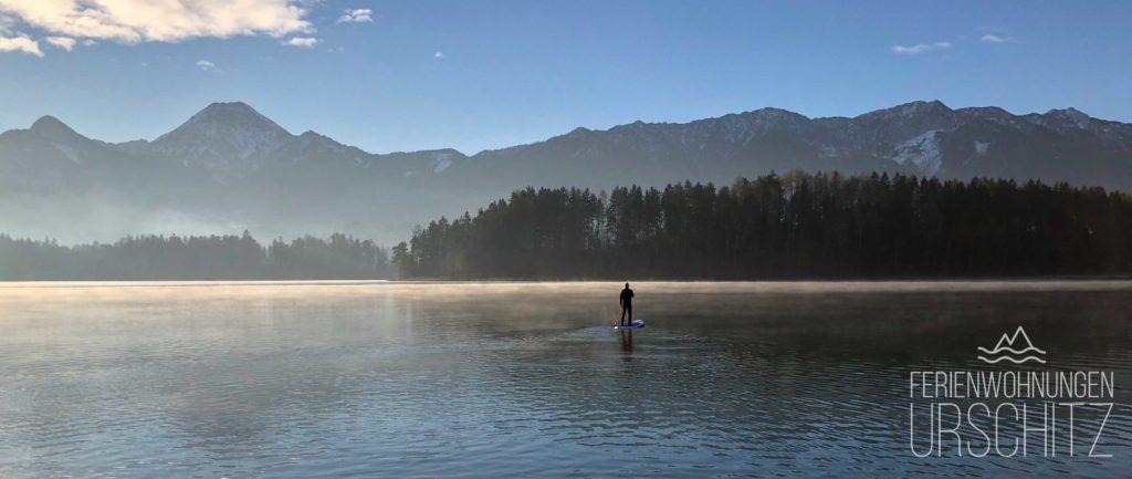 Morgenstimmung am Faaker See beim Winter Stand Up Paddling. Im Hintergrund: Mittagskogel, Faaker See Insel und Halbinsel. Ansicht vom Strandbad Drobollach.