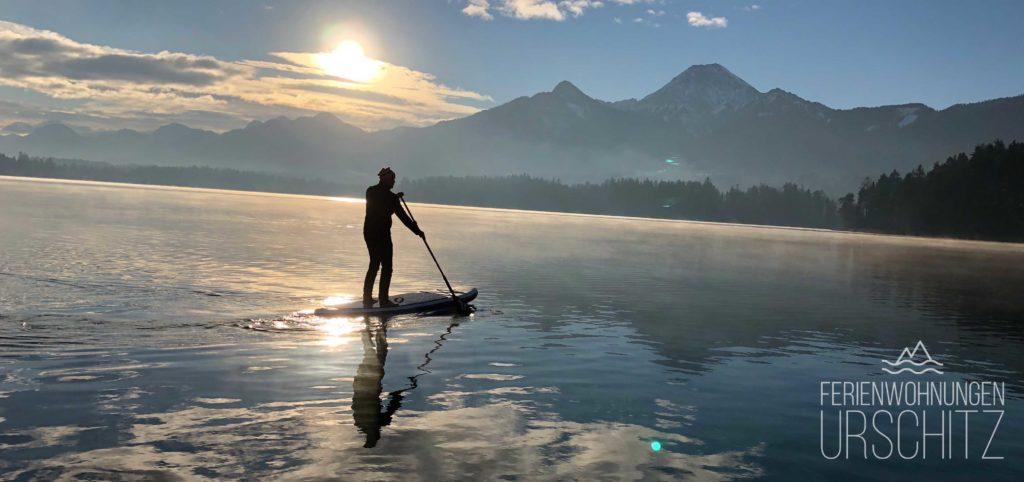 Tiefer Sonnenstand beim SUPen am Faaker See mit Blick auf den Mittagskogel und die Ferlacher Spitze.